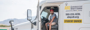 CDL student sits behind the wheel with door open, posing for picture